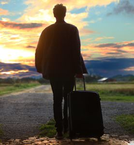 man moving with suitcase into the distance
