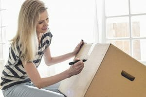 Woman labeling her moving boxes with marker