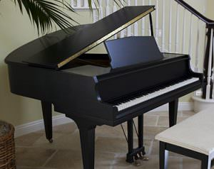 Baby Grand Piano in a persons home by the stairs