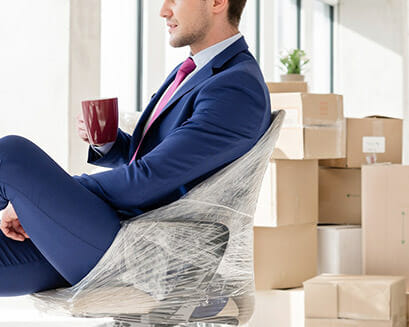 Business man sits back while office movers pack up the office