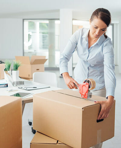 Business woman taping up a moving box in the office