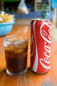 Glass of Coca Cola with coke can next to it