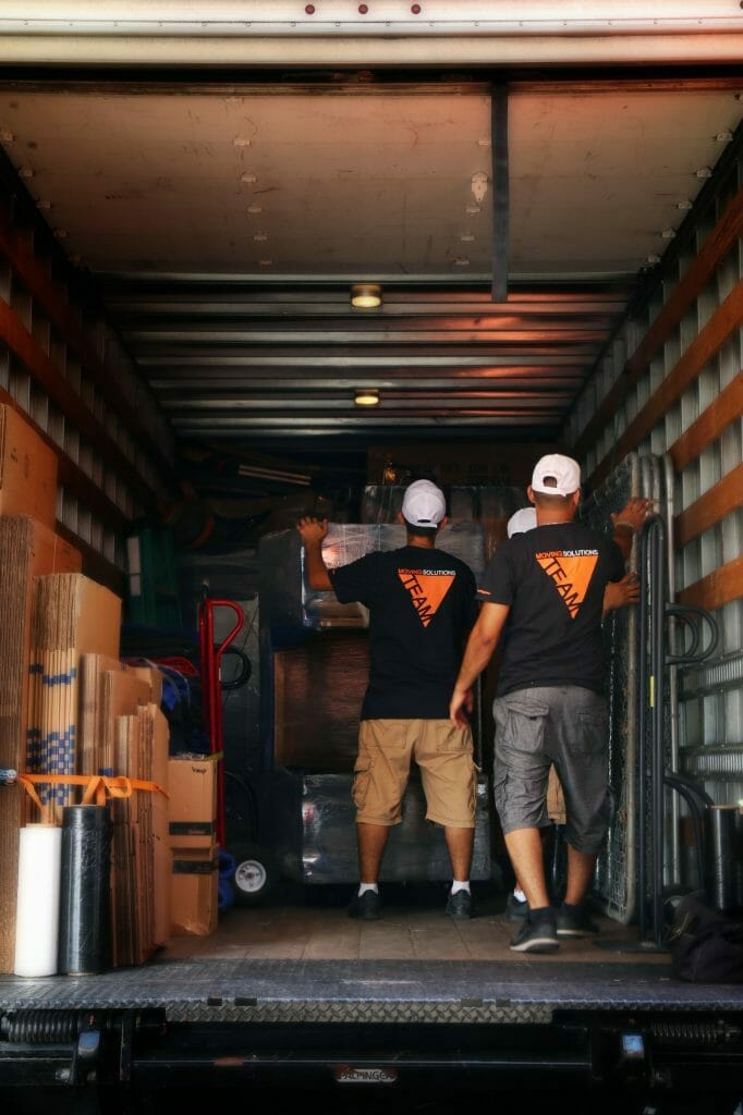 moving men stacking boxes and furniture in truck