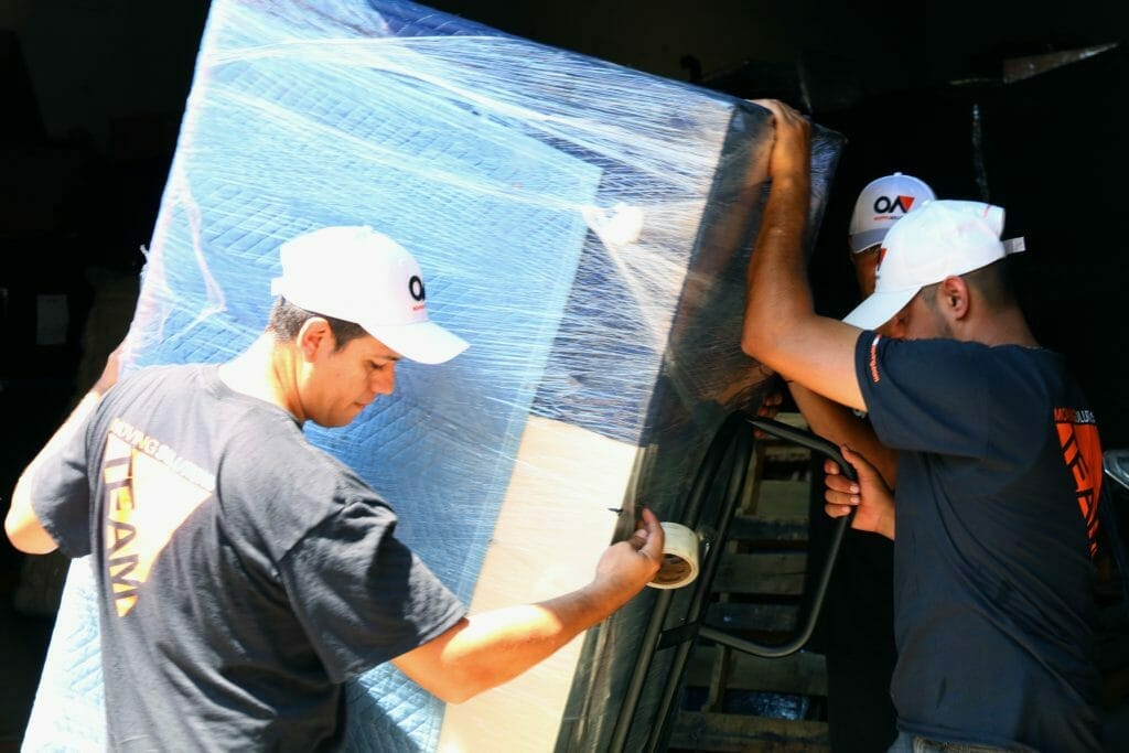 Three movers moving a refrigerator
