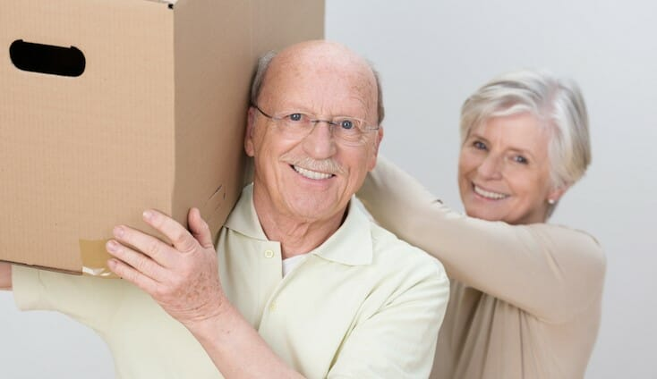 Senior citizen holding a moving box