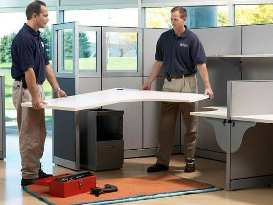 two men assembling office cubicle furniture